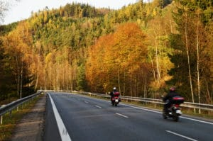 motorcycle riders on the highway during a fall day with bright colored leaves