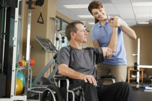 man in a wheelchair getting physical therapy after a spinal cord injury